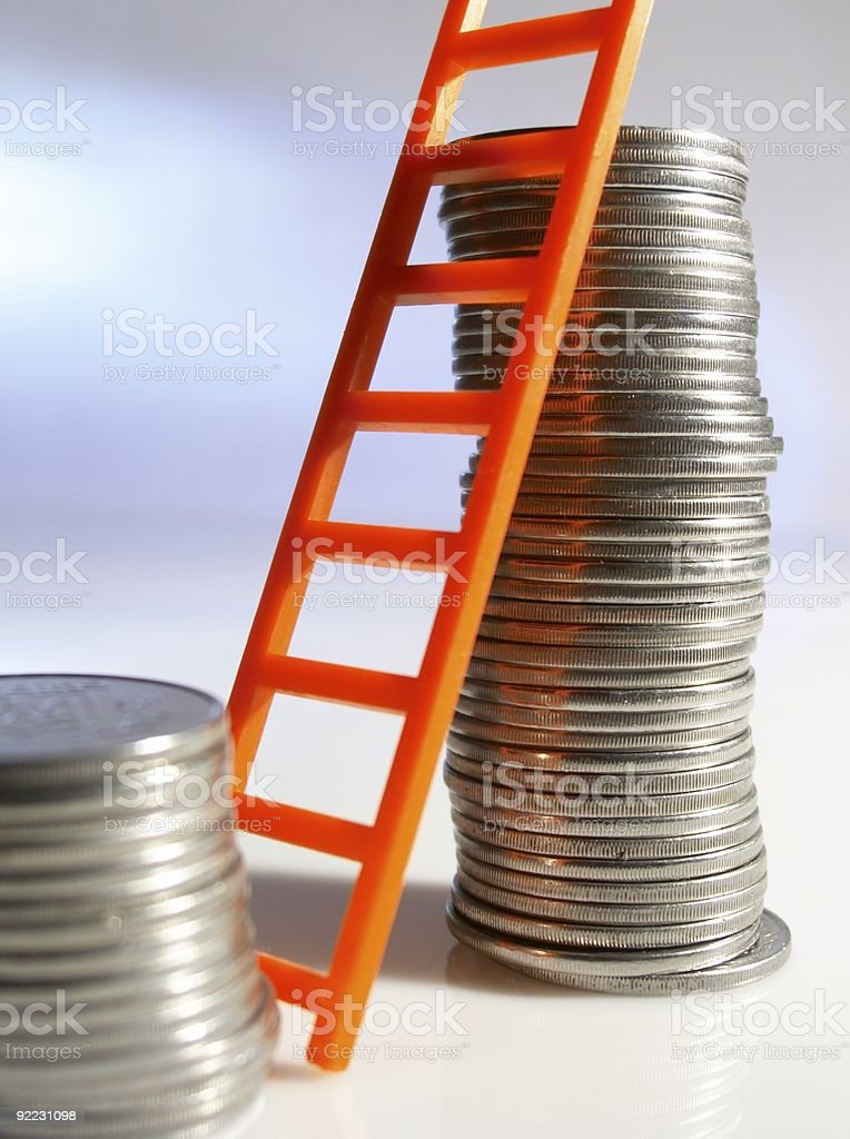 Toy ladder leaning on a pile of coins stock photo