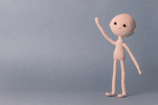 istock A toy man on a gray background with space for text. Knitted toy amigurumi. Presentation. Motivational phrase. Cute model. Puppet. Sweet doll. Hand up 940385762