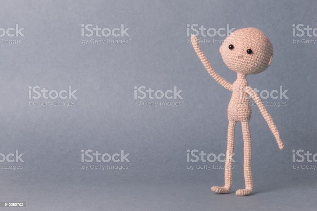 Un hombre de juguete sobre un fondo gris con espacio para texto. Juguete punto amigurumi. Presentación. Frase motivacional. Lindo modelo. Marioneta. Muñeca dulce. Mano hacia arriba - foto de stock