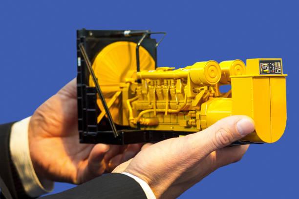 Ein Spielzeugmodell eines Gasgenerator-Sets befindet sich in der männlichen Hand auf blauem Hintergrund. – Foto