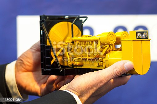 istock A toy model of a gas generator set is in the male hand. Selective focus. 1180041384