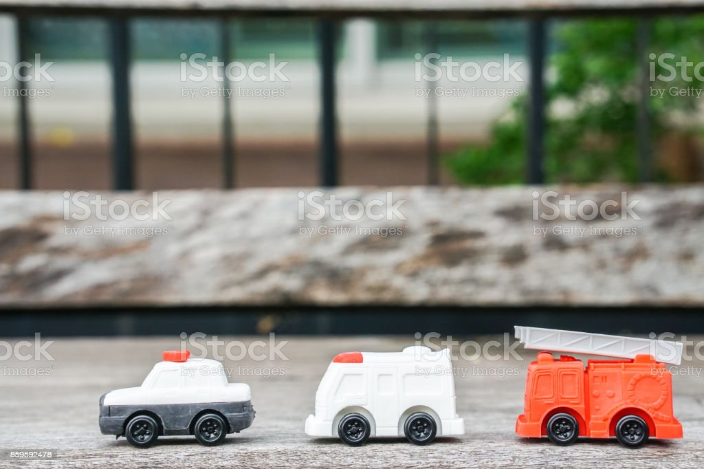 toy model of police car, ambulance van and electricity and utility service truck for kid on wooden floor stock photo