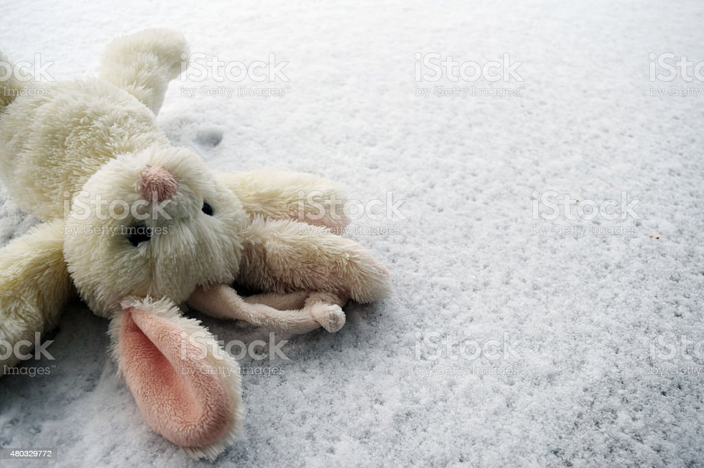 Toy of a bunny lying in the snow stock photo