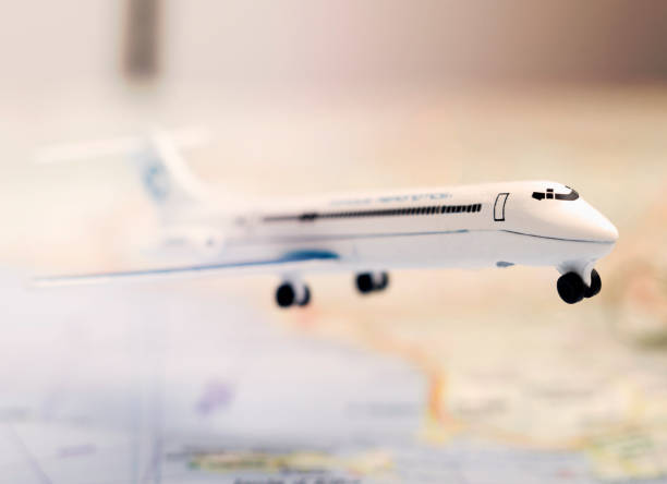 Toy passenger aircraft on the map background, travel concept. Selective focus, toned image. stock photo
