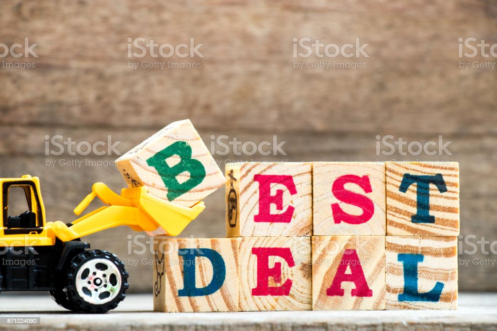Toy plastic bulldozer hold letter block H to complete wording best deal on wood background stock photo