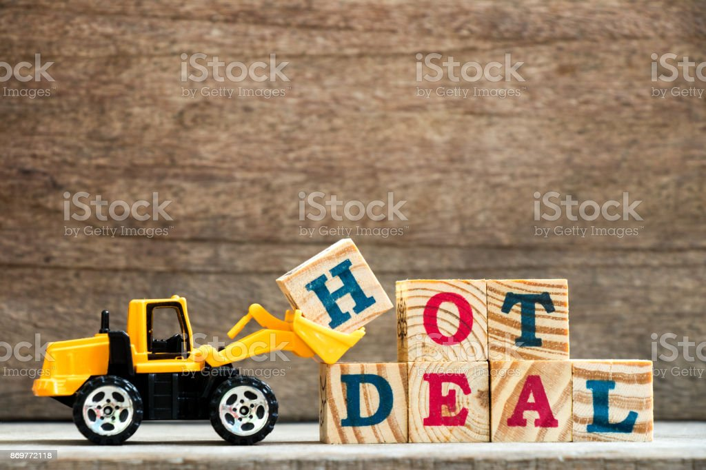 Toy plastic bulldozer hold letter block H to complete wording hot deal on wood background stock photo