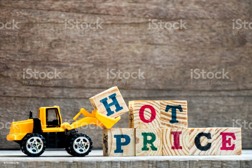 Toy plastic bulldozer hold letter block H to complete wording hot price on wood background stock photo
