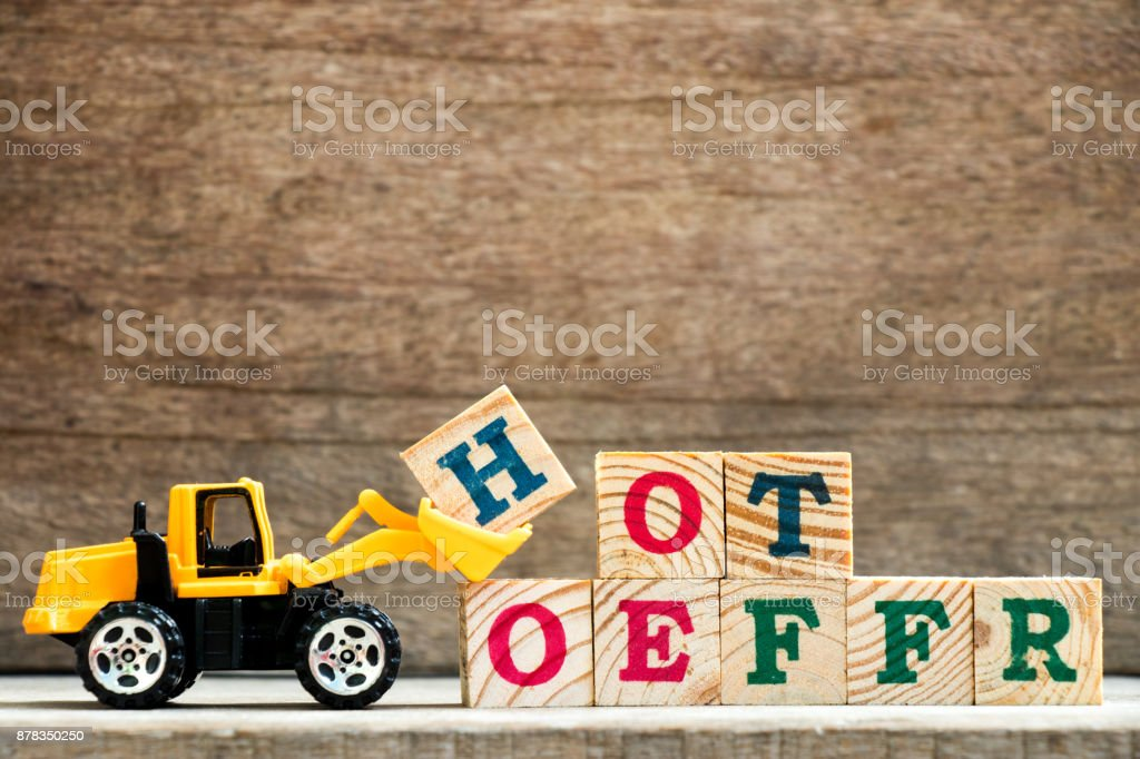 Toy plastic bulldozer hold letter block H to complete wording hot offer on wood background stock photo