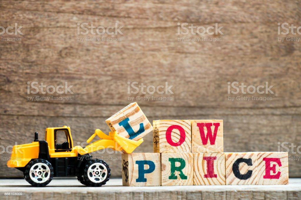 Toy plastic bulldozer hold letter block L to complete wording hot price on wood background stock photo
