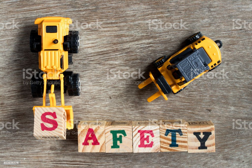 Toy plastic bulldozer hold toy block letter s to fulfill word safety with forklift on wood background - foto stock