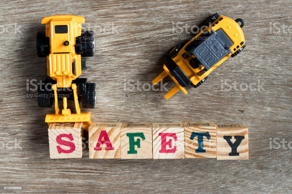 Toy plastic bulldozer hold toy block letter s to fulfill word safety with foklift on wood background - foto stock