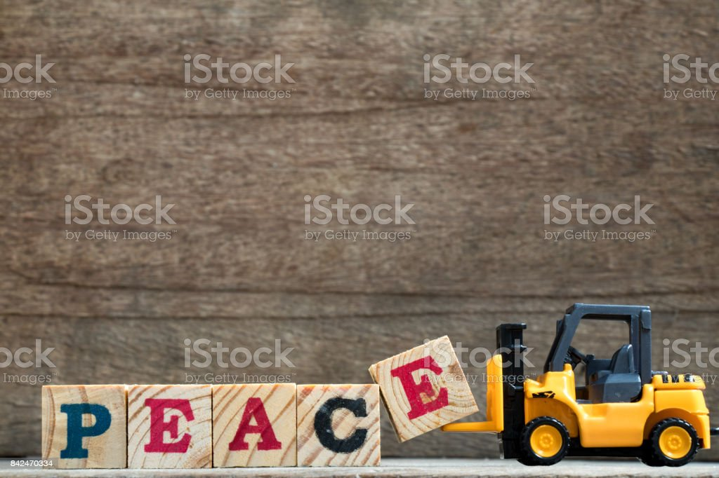Toy plastic forklift hold block E to compose and fulfill wording peace on wood background stock photo