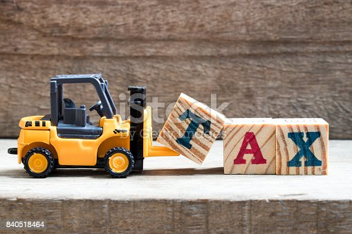 istock Toy plastic forklift hold block T to compose and fulfill wording TAX on wood background 840518464