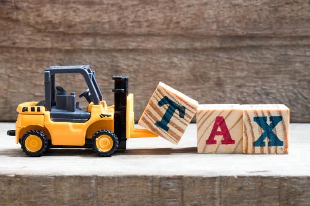 spielzeug aus kunststoff stapler halten block t zu komponieren und zu erfüllen, wortlaut steuer auf holz hintergrund - kindergeldantrag stock-fotos und bilder