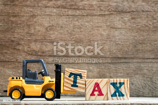 istock Toy plastic forklift hold block T to compose and fulfill wording TAX on wood background 865261066