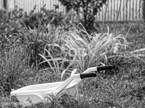 istock toy plastic wheelbarrow in the garden in summer 1221778079