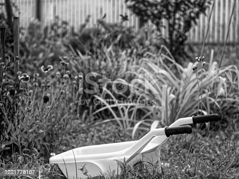 istock toy plastic wheelbarrow in the garden in summer 1221778107