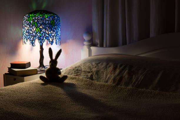 spielzeug hase wieder beleuchtet durch die lampe im schlafzimmer. - lila, grün, schlafzimmer stock-fotos und bilder