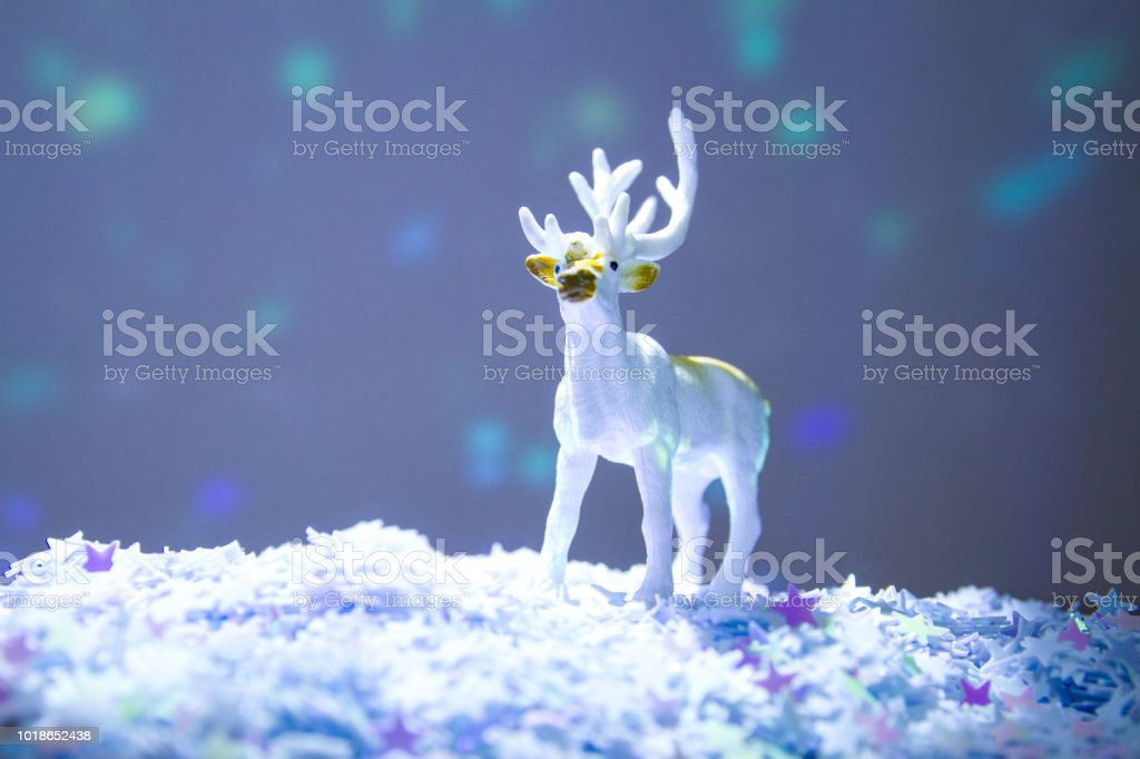 Toy reindeer on glitter star snow with coloured lights behind stock photo