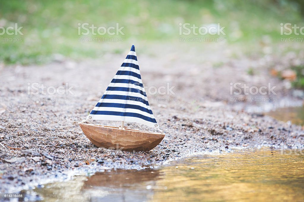 Toy Sailboat With Striped Sail Sitting By Creek - foto de acervo