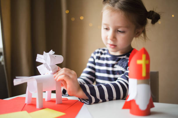DIY toy Saint Nicholas and white horse for sinterklaas day. paper craft for kids. DIY toy Saint Nicholas and white horse for sinterklaas day. create art for children. girl glues horse. sinterklaas stock pictures, royalty-free photos & images