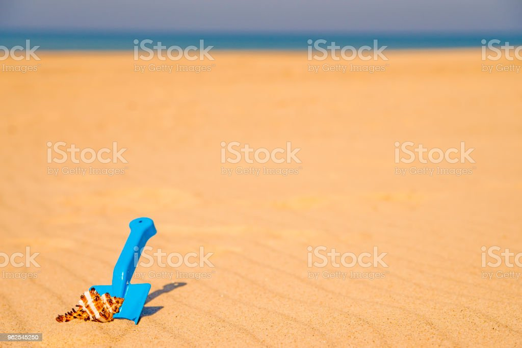 brinquedo, pá com caracol em uma praia ensolarada - Foto de stock de Amarelo royalty-free