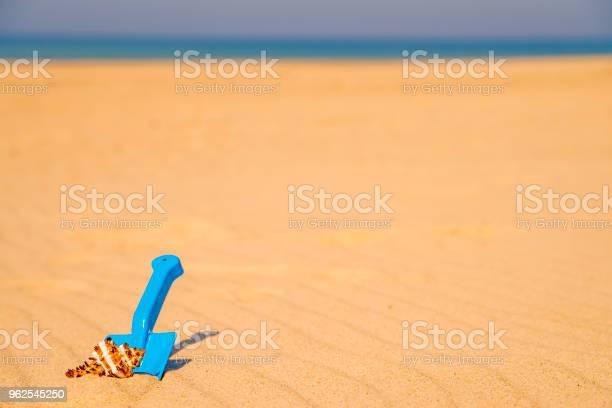 Foto de Brinquedo Pá Com Caracol Em Uma Praia Ensolarada e mais fotos de stock de Amarelo