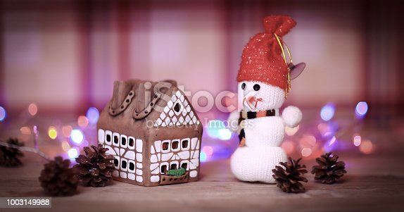 1056829102 istock photo toy snowman and gingerbread house at the Christmas table 1003149988