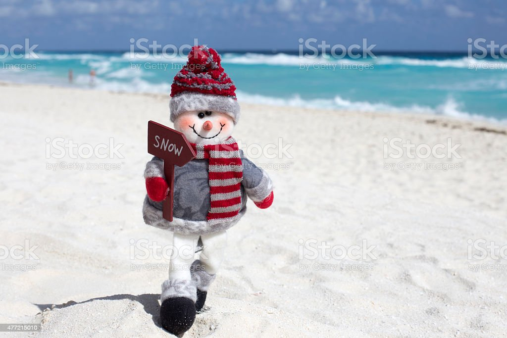 Toy snowman at the beach stock photo