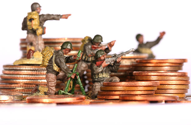 Toy soldiers posed on coin stacks depicting a money war stock photo