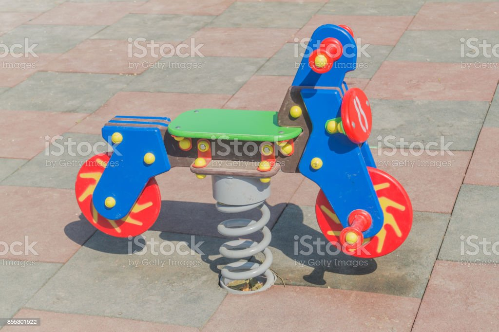 Toy swing motorcycle in the children rubber playground stock photo