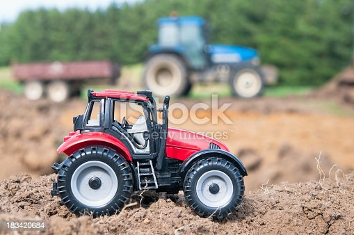 Two tractors outdoors, a toy in the foreground and a real tractor and trailer (defocussed) in the background.