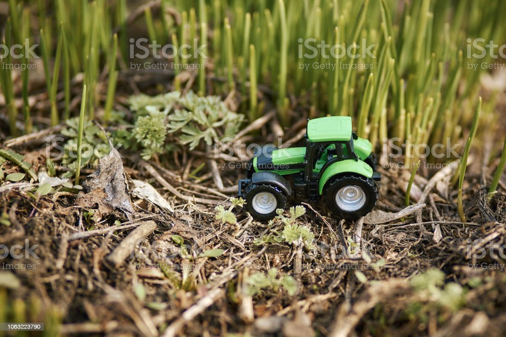 toy tractor on green grass background . Spring sowing works