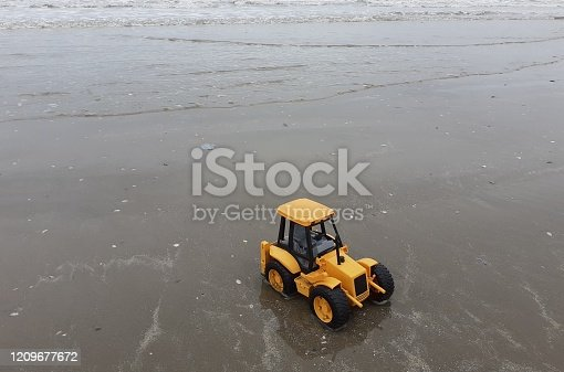 Toy tractor in the sand on Bettystown beach, County Meath, Ireland with the ocean in the background.