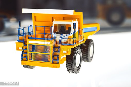 Yellow toy dump truck is isolated on the road