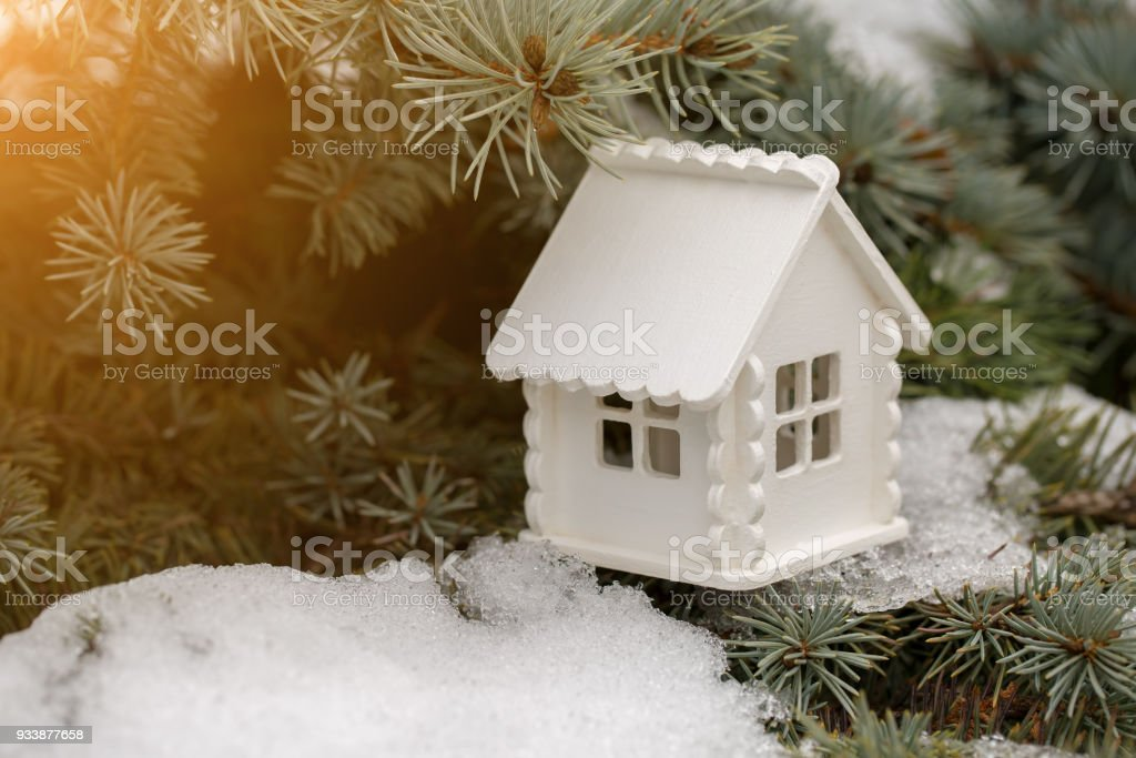 Toy white house is on the pine branch with snow in sunny day stock photo