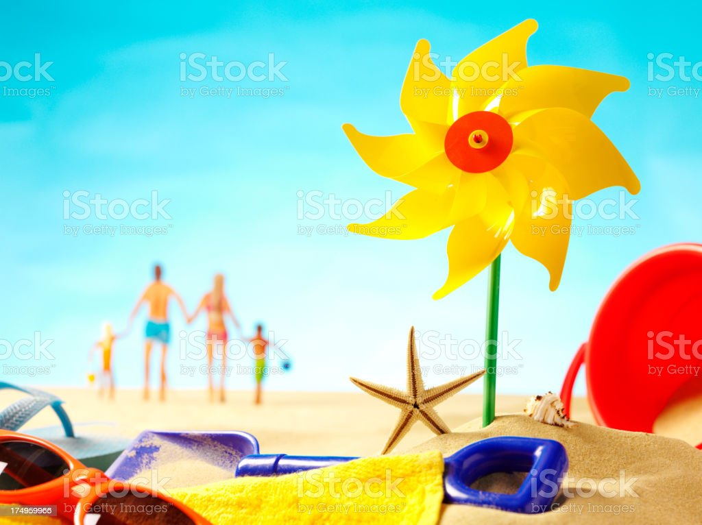 Toy Windmill in the Sand with a Family Holding Hands royalty-free stock photo