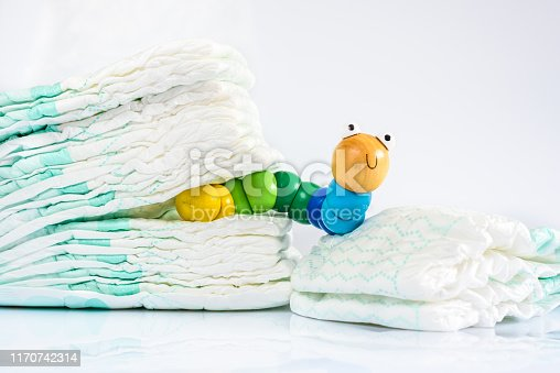 Toy worm with smile next to a pile of diapers, to illustrate concepts of health and childhood intestinal diseases. Isolated on white