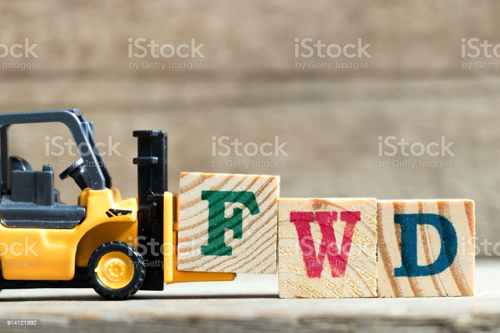 Toy yellow forklift hold letter block F to complete word FWD (Abbreviation of forward)on wood background stock photo