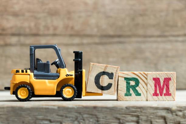 Chariot élévateur jouet jaune tenez bloc lettre pour compléter le mot CRM (abréviation de Customer Relationship Management) sur fond de bois - Photo