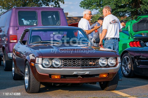 Dartmouth, Nova Scotia, Canada - July 4, 2019 : 1976 Toyota Celica ST at weekly summer A&W Cruise-In at Woodside ferry terminal parking lot. Two men stop and socialize among the classic cars.