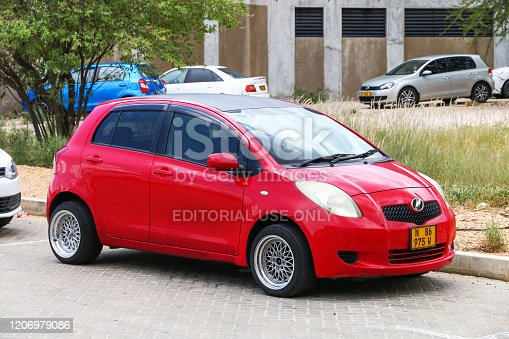 Windhoek, Namibia - February 5, 2020: Red compact car Toyota Yaris in the city street.