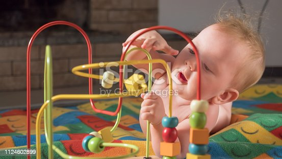 Supporting the development of fine motor skills. Fine motor skills developing. Gifts for toddlers, babies. Colorful toy appealing to hold. Montessori background. Toddler developing fine motor skills.