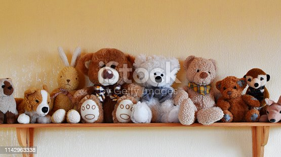 Soft plush toys for children sitting in row on wooden shelf, different toy animals for kids on yellow wall background with copy space.