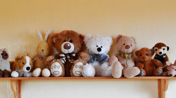 Toys for children sitting in row on wooden shelf Soft plush toys for children sitting in row on wooden shelf, different toy animals for kids on yellow wall background with copy space. fluffy stock pictures, royalty-free photos & images