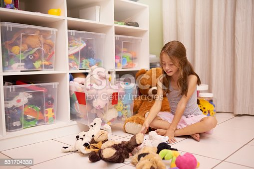 Shot of a young girl playing with toys in a room