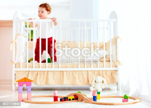 istock toys on the floor in sunny bedroom with infant baby in the crib on background 922774840