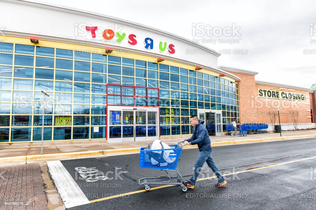 Toys R US store in Fairfax County, Virginia for children shop exterior entrance with sign, logo, doors, closing going out of business bankruptcy, man pushing trolley shopping cart