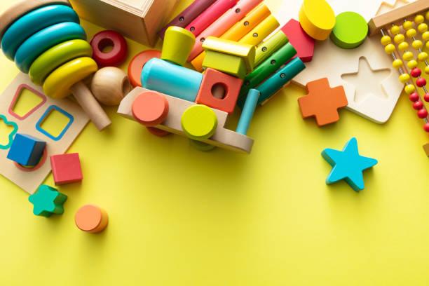 Toys: Wooden Toys on Yellow Background Still Life stock photo