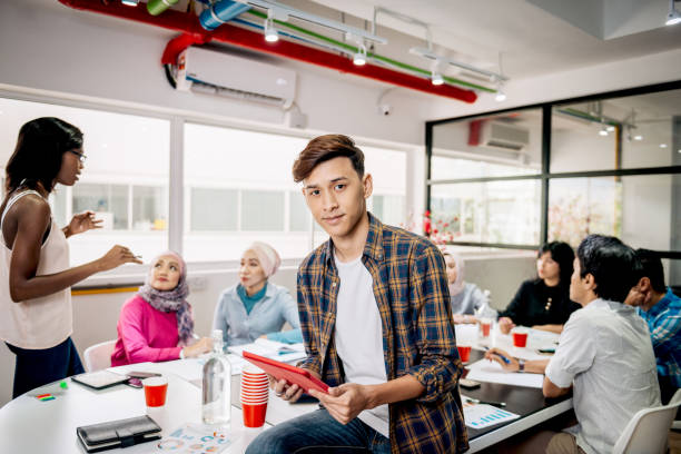 Trabajo en equipo en una nueva compañía con empleados multiétnicos Business development concept and teamwork in new start-up company in South East Asia with ethnically and age diverse business people trabajo en equipo stock pictures, royalty-free photos & images